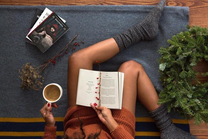 Žena na zemi na dese s kávou a knihami