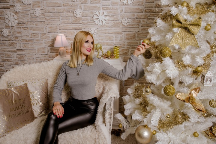 Žena obdivuje bílý vánoční stromeček.
