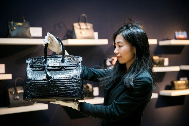 Žena oblečená v černém si v butiku prohlíží kabelku z krokodýlí kůže