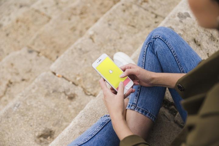 Žena se připojuje k mobilní aplikaci Snapchat