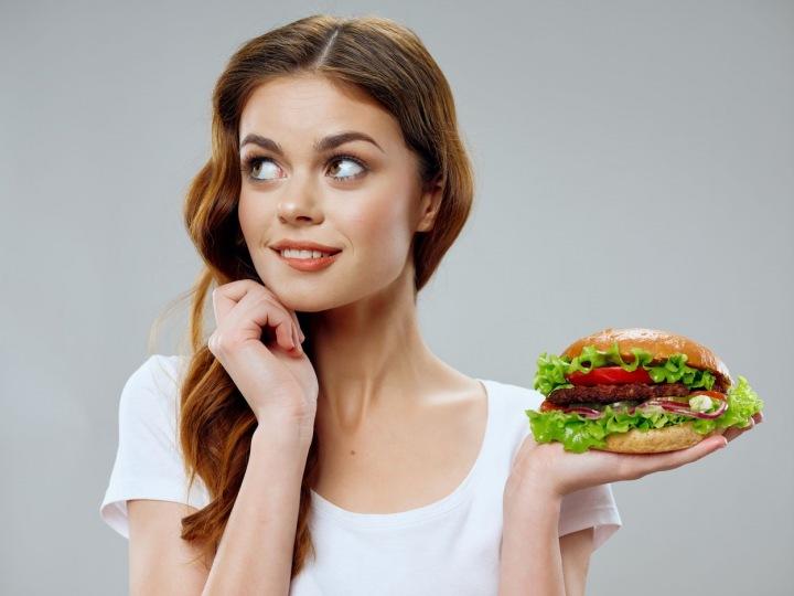 Krásná mladá dívka s hamburgerem v ruce