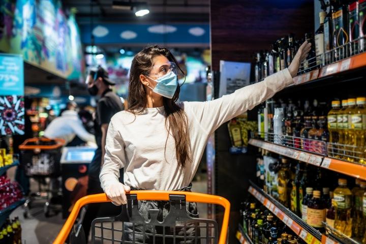 Žena s rouškou nakupuje v supermarketu