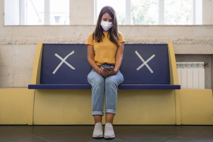 Žena s rouškou sedí na zastávce