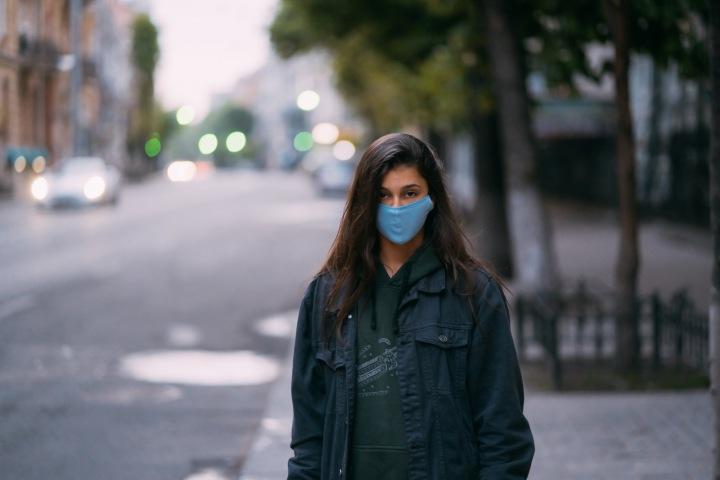 Žena s rouškou stojí na ulici