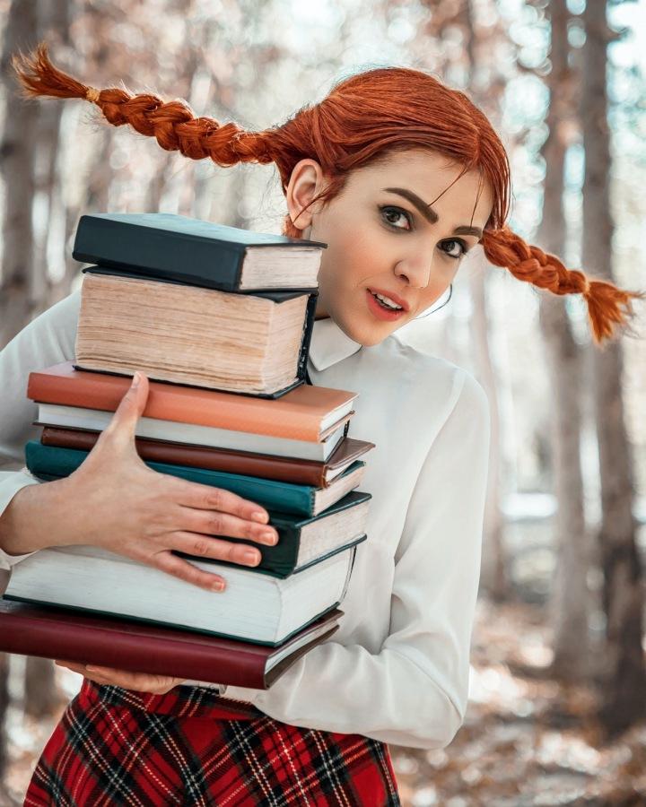 Žena se zrzavými vlasy a s knihami v rukách