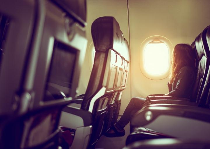 Žena sedí v letadle a dívá se z okénka