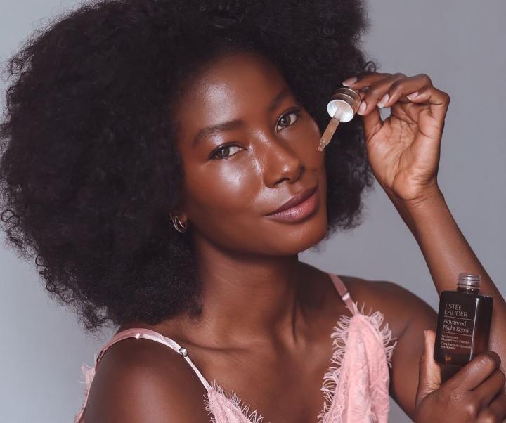 Žena si na tvář aplikuje kosmetiku Estée Lauder