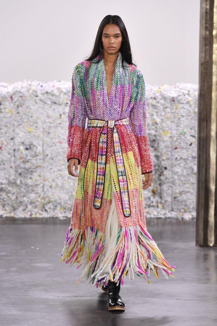 Žena v barevném kabátu s třásněmi značky Gabriela Hearst