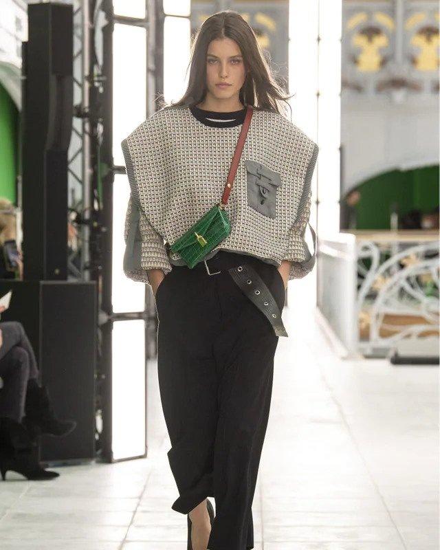 Žena v černých kalhotách a šedém topu Louis Vuitton SS2021