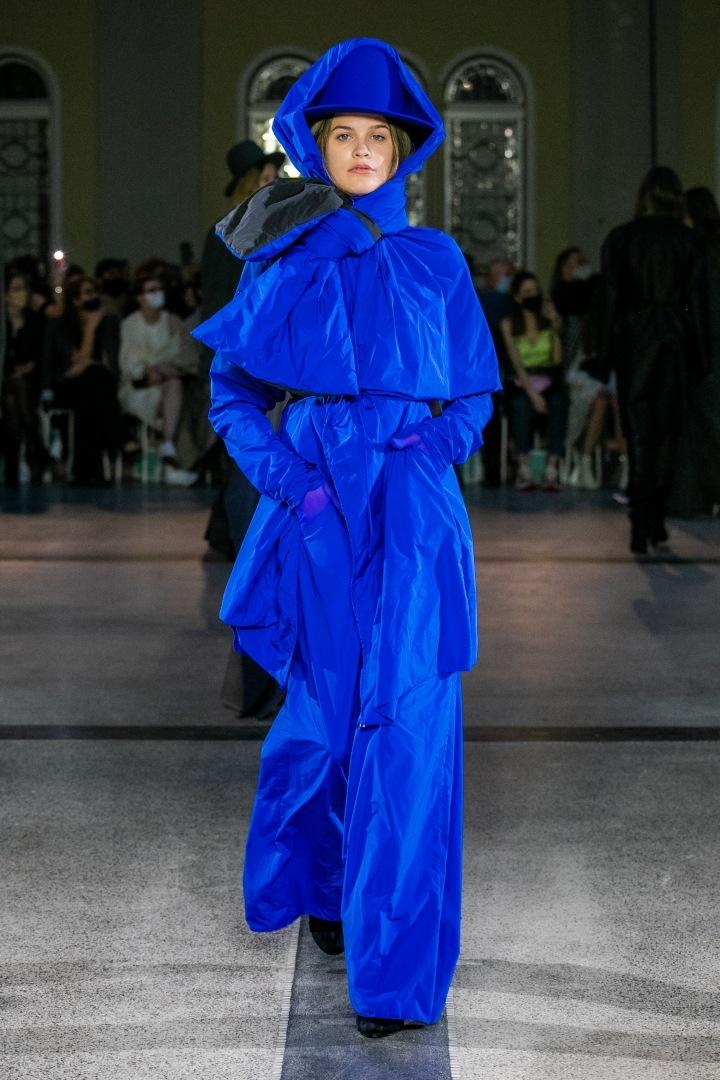 Žena v modrém outfitu s kapucí od Jakuba Polanky