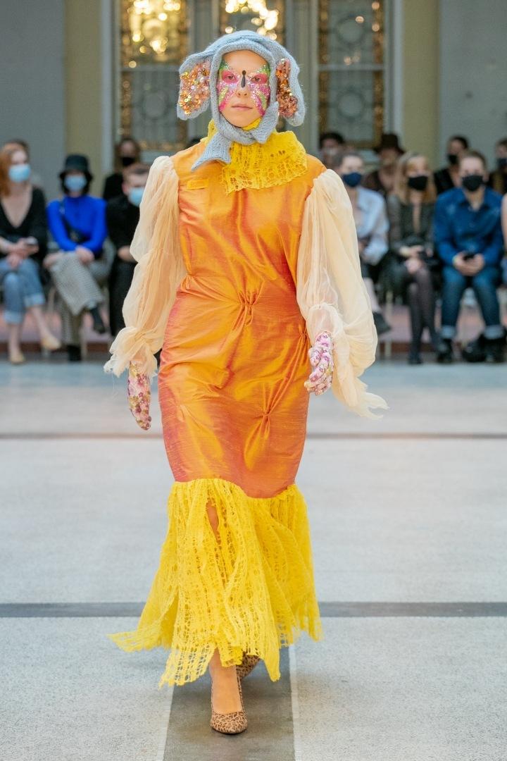 Žena v oranžových šatech a šedé čepici