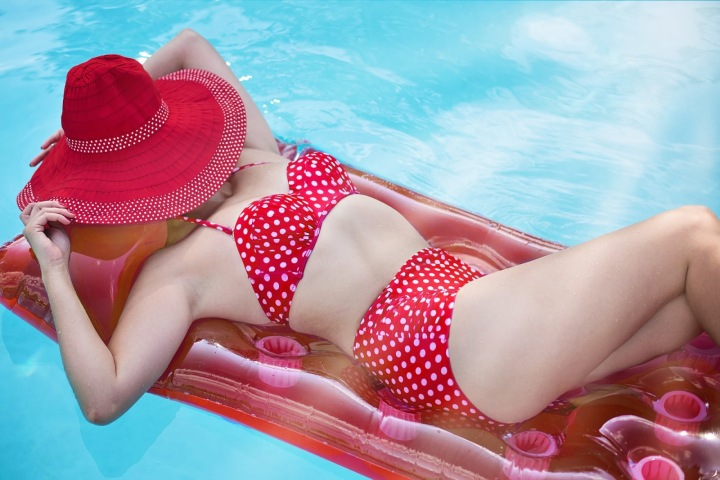 Žena v plavkách se opaluje u bazénu.