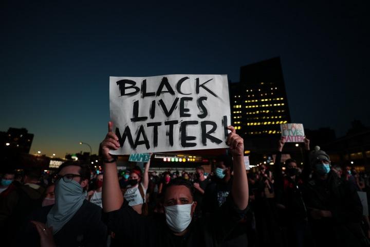Žena v roušce drží nad hlavou plakát Black lives matter
