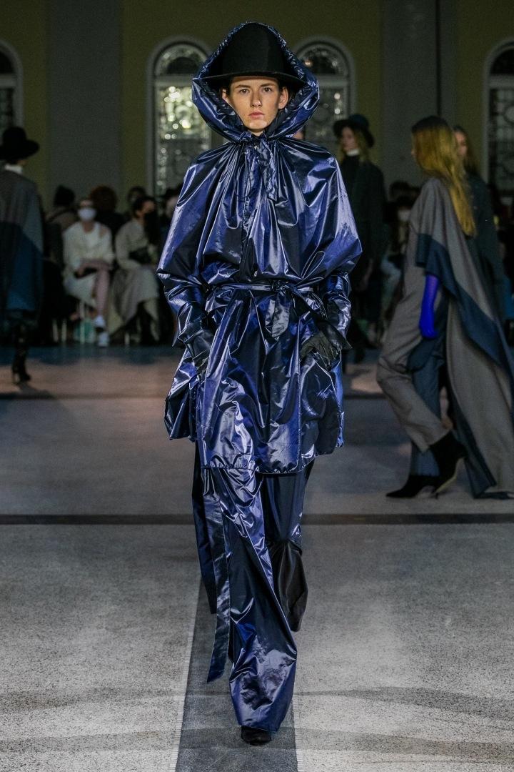 Žena v tmavě modrém outfitu s kapucí od Jakuba Polanky