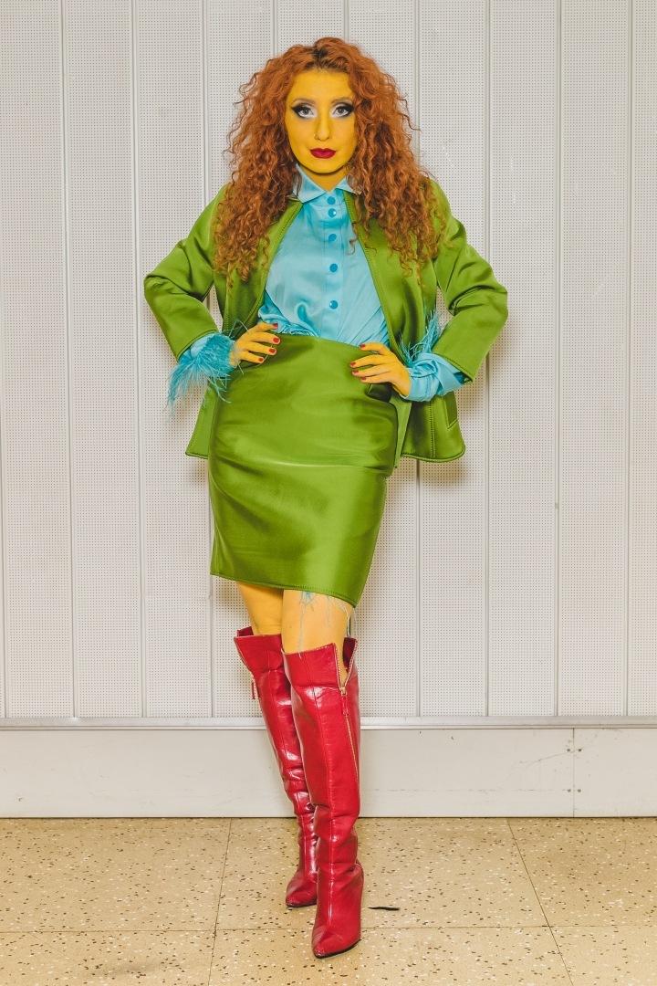 Žena v zeleném kostýmku, modré halence a červených kozačkách Lukáše Krnáče