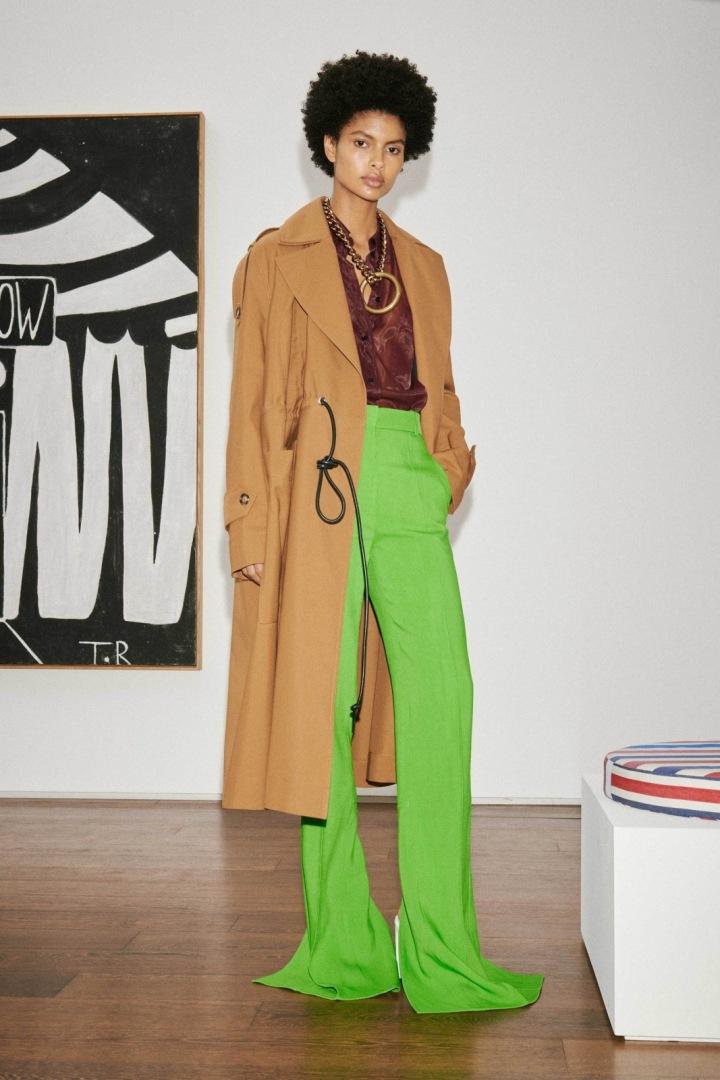 Žena v zelených kalhotách a béžovém kabátu Victoria Beckham