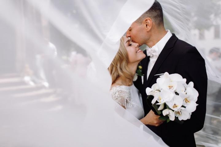 Ženich líbá nevěstu na čelo.