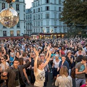 Lidé se baví a tančí v ulicích během festivalu Fête des Vendanges de Montmartre.