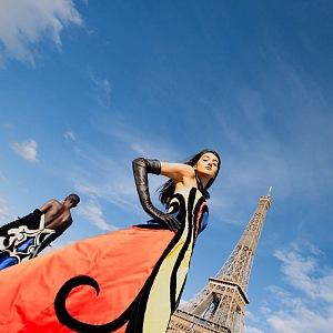 Žena v barevných šatech Balmain pod Eiffelovou věží