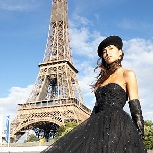 Žena v černých šatech Balmain pod Eiffelovou věží