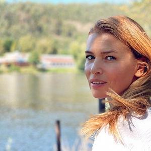 Daniela Peštová se usmívá, za ní je příroda