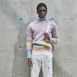Muž v bílých kalhotách a barevném svetru Dior