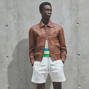 Muž v šortkách a kožené bundě Dior