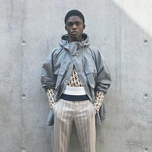 Muž v béžových kalhotách a šedé bundě Dior