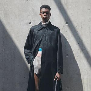 Muž v šortkách a černém kabátu Dior