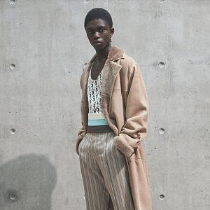Muž v béžových kalhotách a béžovém kabátu Dior