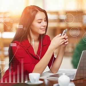 Elegantní žena u počítače s telefonem v ruce, připojena na sociální sítě