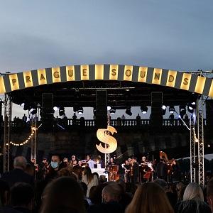 Hudebníci hrající na pódiu, nad nimi nápis Prague Sounds