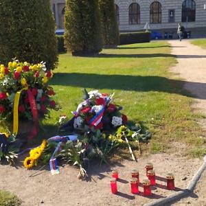 Před Rudolfinem lidé pokládají květiny a svíčky.