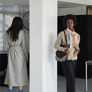 Žena v béžovém trenčkotu a černých kalhotách Louis Vuitton