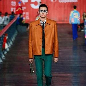 Muž v oranžové bundě a zelených kalhotách Louis Vuitton SS 2021