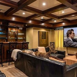 Multimediální místnost s barem, koženou sedačkou a televizí