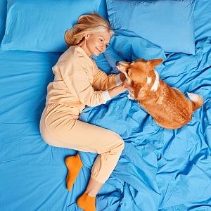 Žena se mazlí se psem v posteli