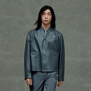 Muž v šedých kalhotách a kožené bundě Prada
