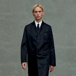 Muž v černém obleku a kabátu Prada