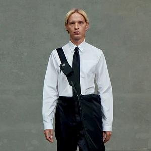 Muž v černých kalhotách a bílé košili Prada