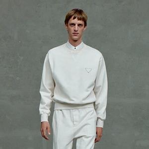 Muž v bílých kalhotách a mikině Prada