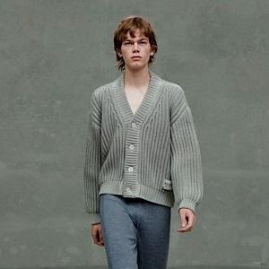 Muž v teplákách a pleteném svetru Prada