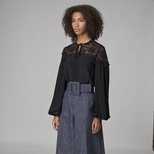 Žena v černé halence a širokých kalhotech