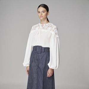 Žena v bílé halence a širokých kalhotech