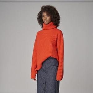Žena v oranžovém svetru a modré sukni