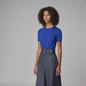 Žena v modrém topu a širokých kalhotech
