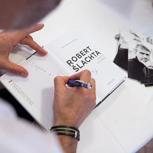 Robert Šlachta podepisuje svou knihu.