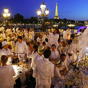Lidé oblečeni v bílé, oslavují bílou noc v Paříži.