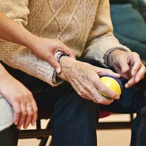 Ruce sedících seniorů, jeden drží míček
