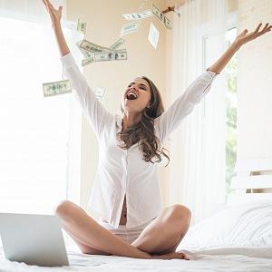 Krásná žena sedící na posteli a rozhazující peníze